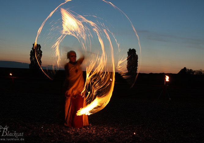 Das Bild zeigt einen Gaukler nachts bei einer Feuerdarbietung im Themenpark Weltentor
