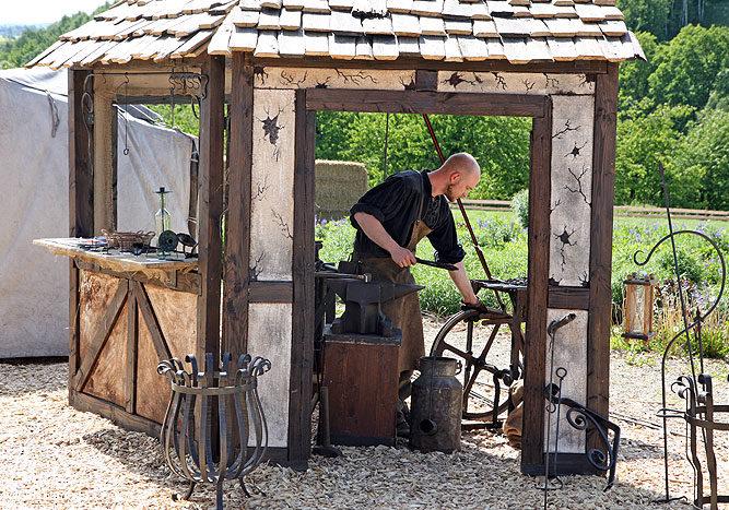 Das Bild zeigt den Schmied bei seiner Arbeit in der Schmiede im Themenpark Weltentor